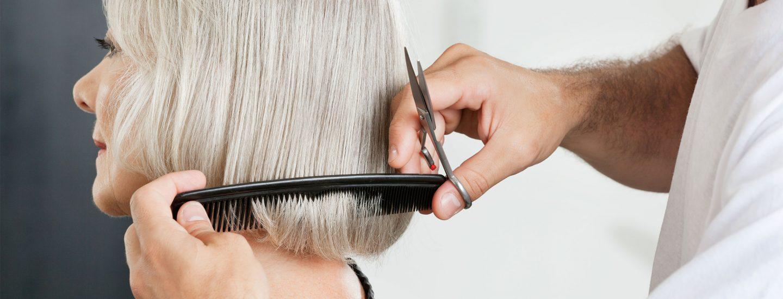 Friseur beim Haareschneiden einer älteren Dame